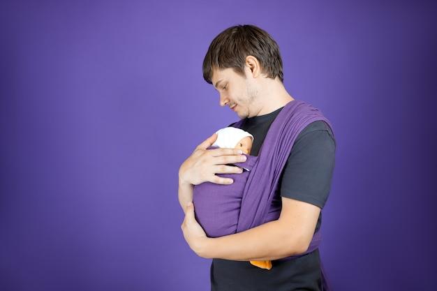 若い男が父親になることを学んでいます。人形に赤ちゃんを着せる訓練。子育てコース。