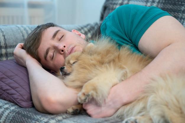 若い男が目を閉じて横になって寝て、日中ソファで昼寝をしている