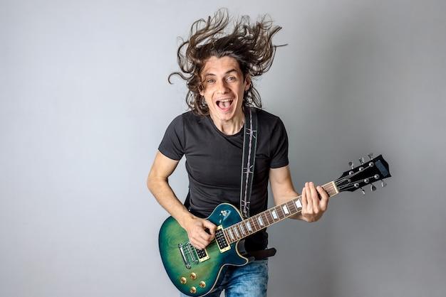 若い男が長い髪を歌って手を振っているエレキギターを弾いています