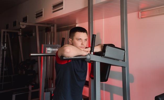 Молодой человек отдыхает после тренировки в тренажерном зале. задумчивый взгляд
