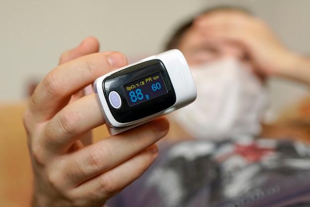 한 젊은이가 covid-19 코로나바이러스에 감염되어 집에서 소파에서 산소 포화도를 측정합니다. 맥박 산소 농도계 휴대용 디지털 장치 코비드-19 바이러스성 폐렴. 선택적 초점입니다.