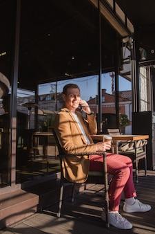 若い男が電話で話し、笑顔でコーヒーを飲みながらカフェに座っています