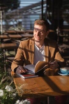 젊은 남자가 커피와 미소를 마시는 비즈니스 회의를 기다리는 카페에 앉아있다