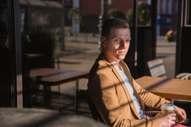若い男がコーヒーを飲みながら何かを考えている会議を待っているカフェに座っています
