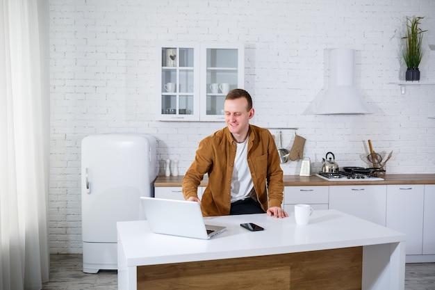 На кухне сидит молодой человек с ноутбуком и разговаривает по телефону. удаленная работа.