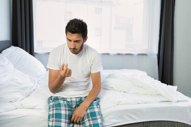 한 젊은 남자가 침대에 앉아있다. 그는 역가와 관련된 문제로 고통 받고 있습니다.