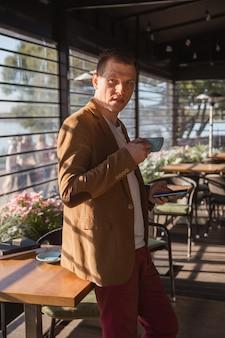 젊은 남자가 커피를 마시고 전화를 들고 비즈니스 회의를 기다리는 카페에 서 있다