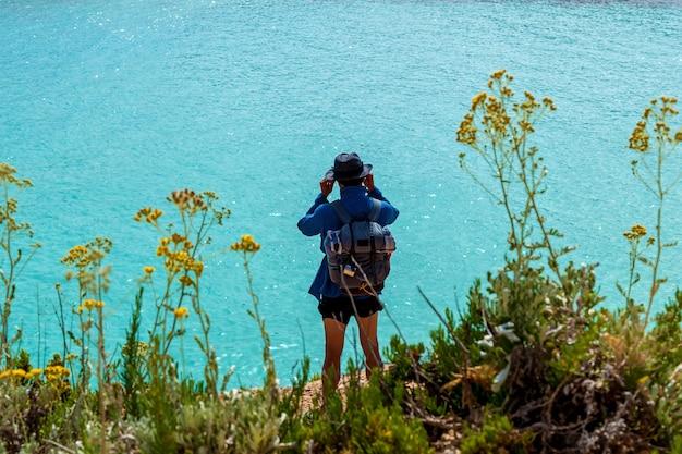 한 젊은이가 해안에 서서 쌍안경으로 바다의 수평선을 바라보고 있습니다.