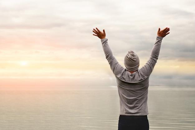 한 젊은이가 해안에 서있다. 뒤에서 본 모습. 요가 수업. 손을 들었다. 자유와 성취.
