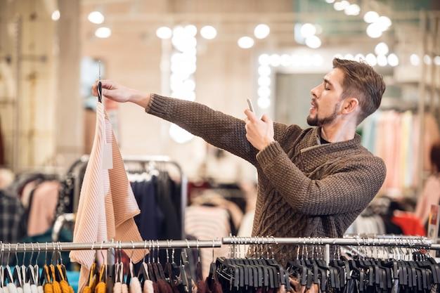 Молодой человек фотографирует предмет в магазине одежды