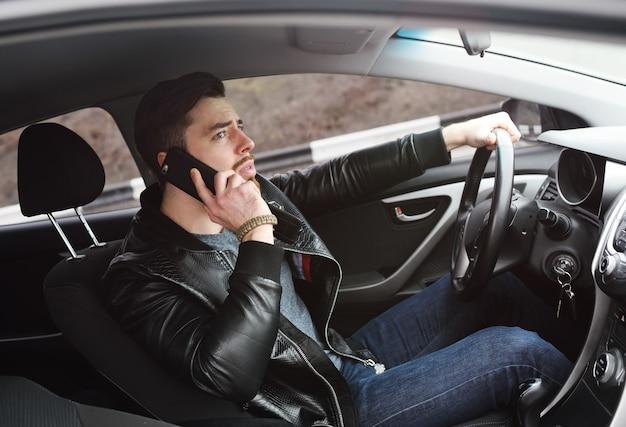 車を運転しているときに若い男が電話で話している。