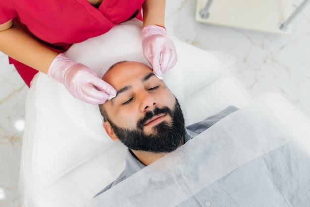 Молодой человек проходит процедуру косметического пилинга лица. косметология и омоложение.