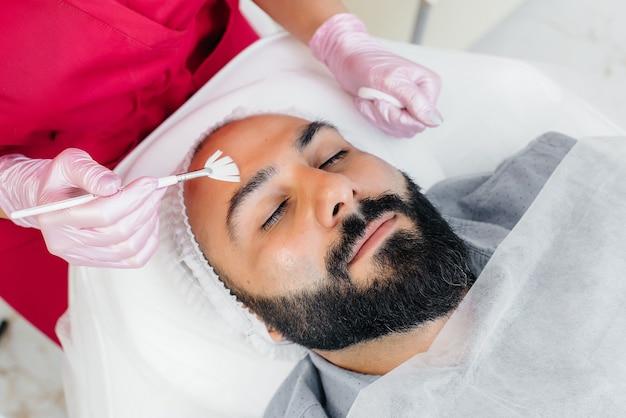 Молодой человек проходит процедуру косметического пилинга лица