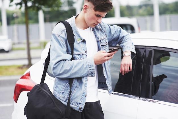 若い男が空港で乗客を待っています。