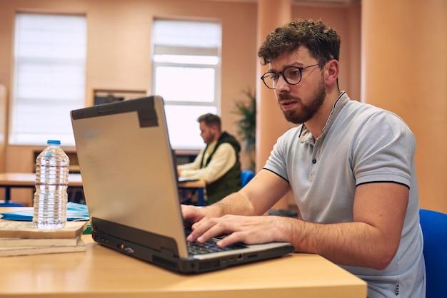 Молодой человек работает со своим ноутбуком в библиотеке