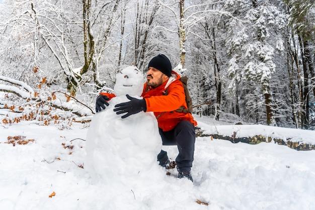 Молодой человек шутит со снеговиком в заснеженном лесу природного парка артикуца в оярцун близ сан-себастьяна, гипускоа, паис васко. испания