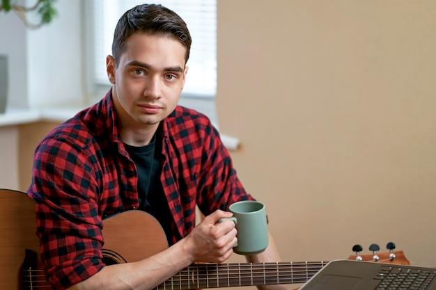 Молодой человек учится игре на гитаре с помощью интернета, ноутбука, онлайн-урока