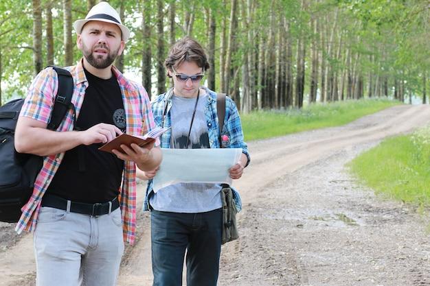 젊은이는 길을 잃지 않기 위해 자연 속에서 지도를 본다