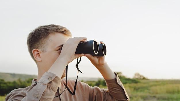 한 청년이 쌍안경을 통해 아름다운 구릉 풍경을 바라보고 있습니다. 사냥, 여행, 야외 레크리에이션의 개념입니다. 복사 공간이 있는 배너입니다. 여행자나 사냥꾼이 쌍안경을 통해 관찰하고 있습니다.