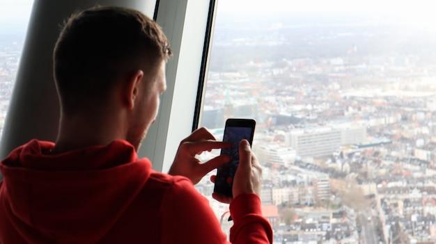 Молодой человек фотографирует городской пейзаж на смартфон. концепция туризма. мужчина фотографирует город со смотровой площадки через стекло с высоты.