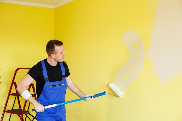若い男がアパートを修理し、壁を別の色で塗り直します