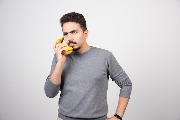 바나나를 전화로 들고 젊은 남자 모델.