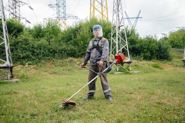 작업 바지에 전기 변전소의 영역에서 잔디를 깎는 젊은 남자. 기업의 잔디 청소, 화재 안전 조치 구현.