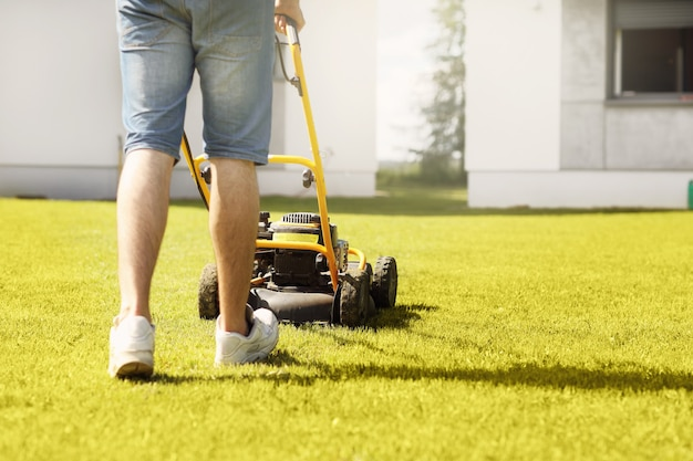 Молодой человек косит газон