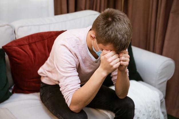 Молодой человек кавказской внешности сидит дома на диване, держит голову в защитной маске с ...