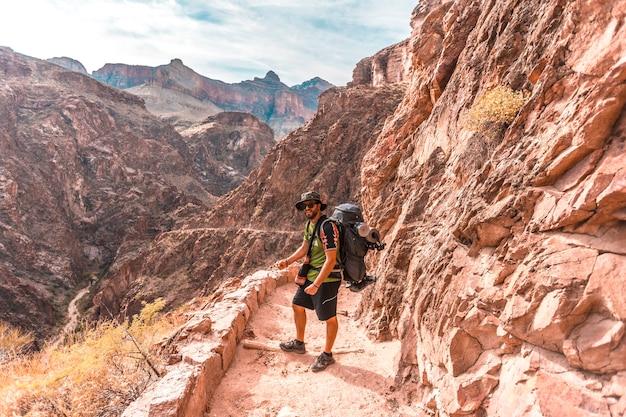 Молодой человек на тропе яркого ангела в гранд-каньоне. аризона