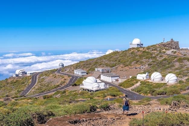 Caldera de taburiente, la palma, canary islands 꼭대기에있는 roque de los muchachos 국립 공원의 망원경을보고있는 흔적에있는 젊은이. 스페인