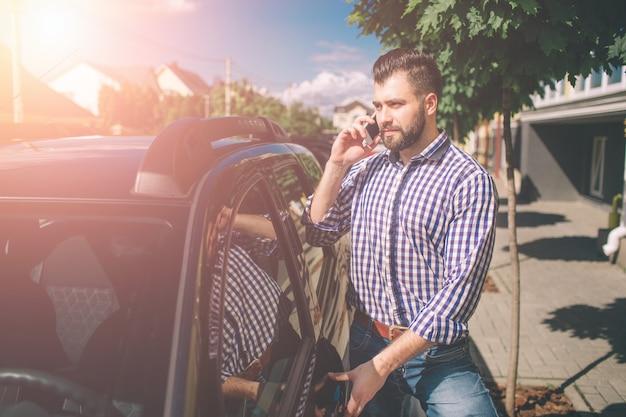 자동차 벽에 젊은 남자. 그의 차 근처에 서서 휴대 전화를 들고 수염을 가진 젊은 매력적인 남자