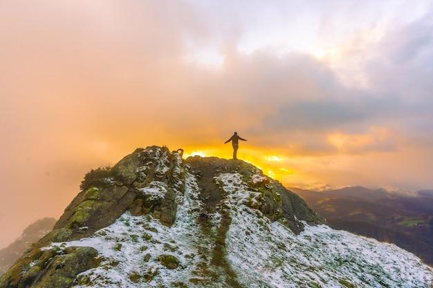 スペイン、サンセバスチャン近くのオイアルツンの町のペーニャスデアヤ山にある、雪の降る冬のオレンジ色の夕日の山の頂上にいる若い男