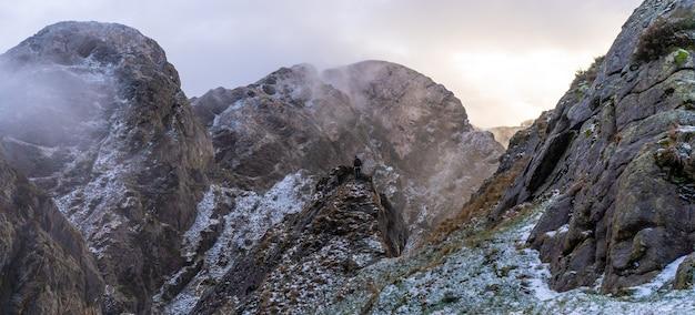 スペイン、サンセバスチャン近くのオイアルツンの町のペーニャスデアヤ山にある、雪の降る冬の日没の山の頂上にいる若い男