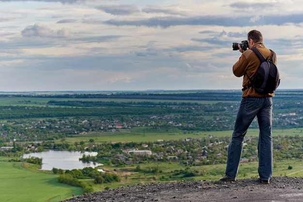 Молодой человек фотографирует сельский пейзаж с высоты птичьего полета.