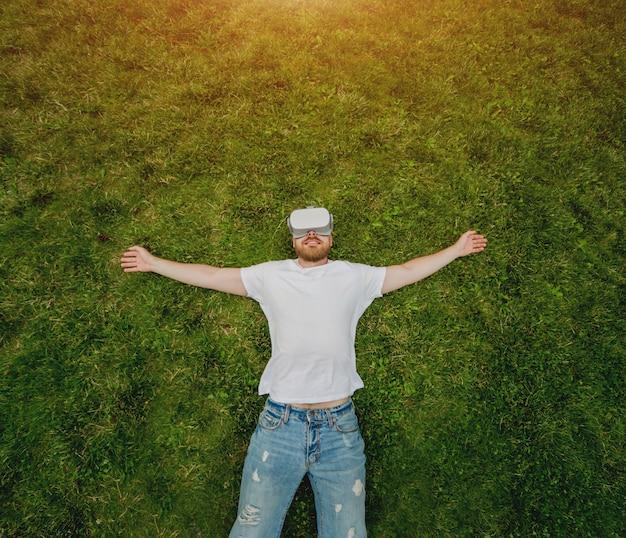 若い男が草の上に横たわっている仮想現実のメガネでゲームをプレイします。