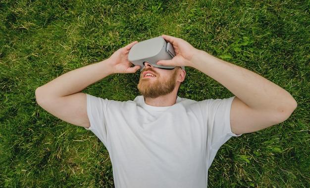 젊은 남자는 잔디에 누워 가상 현실 안경에서 게임을 재생합니다.