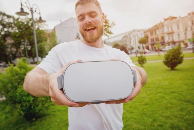 若い男が通りで仮想現実の眼鏡をかけてゲームをプレイします。