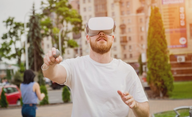 Молодой человек играет в игру в очках виртуальной реальности на улице.