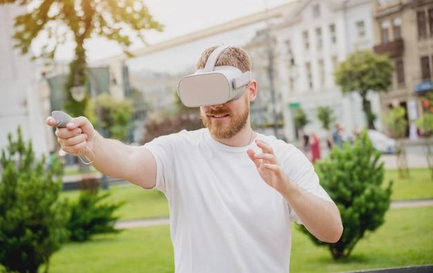 한 젊은이가 거리에서 가상 현실 안경을 쓰고 게임을한다.