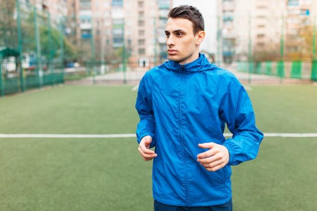 若い男がスポーツをし、サッカーのフィールドを走っています。その男は開放的で新鮮な空気の中で働いています。