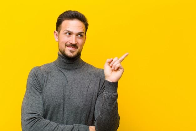 Молодой человек позирует, указывая пальцем в сторону