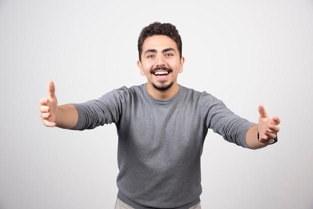 카메라를 향해 손을 당기는 젊은 남자.