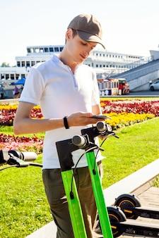 若い男性がスマートフォンでqrコードをスキャンして電動スクーターを借りています。駐車場を共有する際にスクーターを蹴ります。