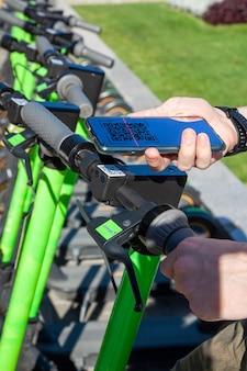 若い男がスマートフォンでqrコードをスキャンして電動スクーターを借りる