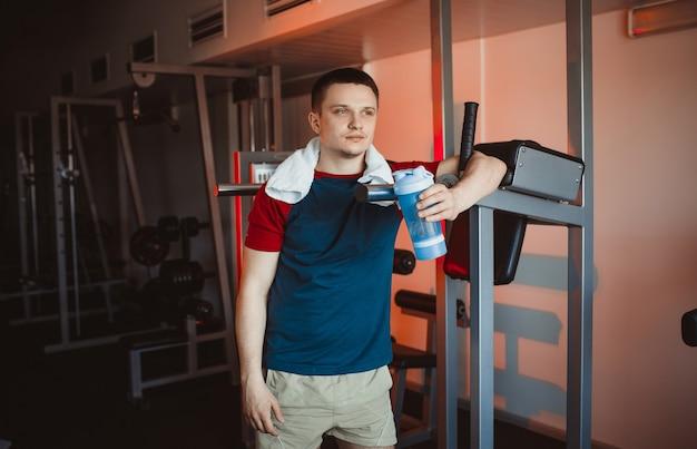 Молодой человек отдыхает после тренировки в тренажерном зале, держа в руке шейкер. задумчивый взгляд