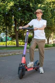 若い男が公園で借りた電動スクーターに乗る