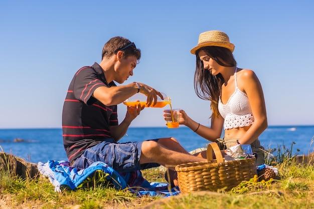 Молодой человек подает апельсиновый сок своей подруге в горах у моря, наслаждаясь теплом