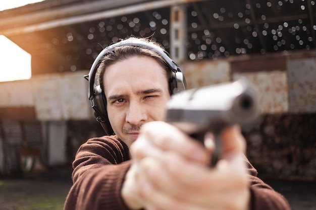 Молодой человек стреляет из пистолета, целится в цель. мужчина в защитных наушниках.