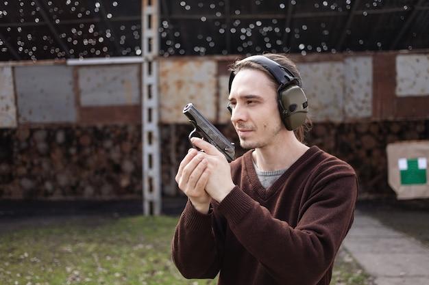 젊은 남자가 목표물을 겨냥하여 총을 쏜다. 보호용 헤드폰을 착용하는 남자.